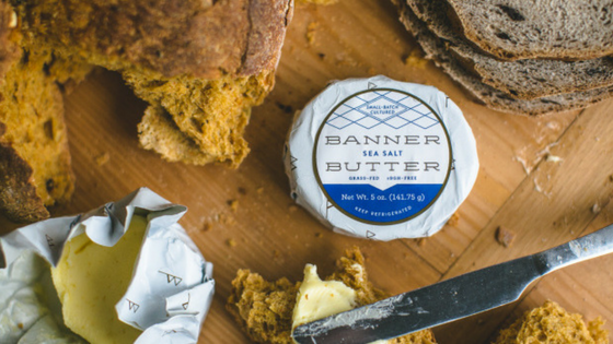 Banner Butter on wood prep station with bread